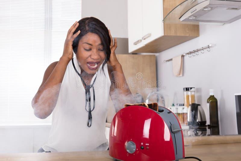 Mujer frustrada que mira la tostada quemada que sale de la tostadora imagenes de archivo