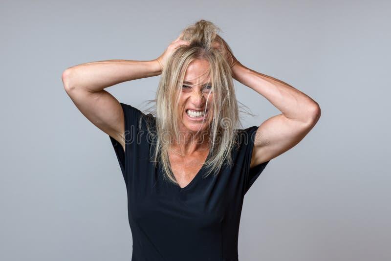 Mujer frustrada que rasga en su pelo rubio largo imagenes de archivo