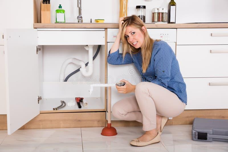Mujer frustrada que tiene problema del fregadero de cocina foto de archivo libre de regalías