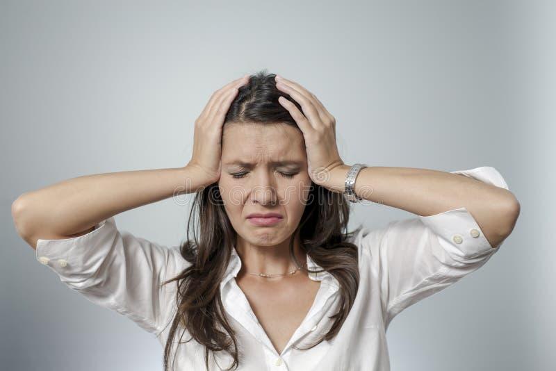 Mujer frustrada que toma su cabeza entre sus manos imagenes de archivo