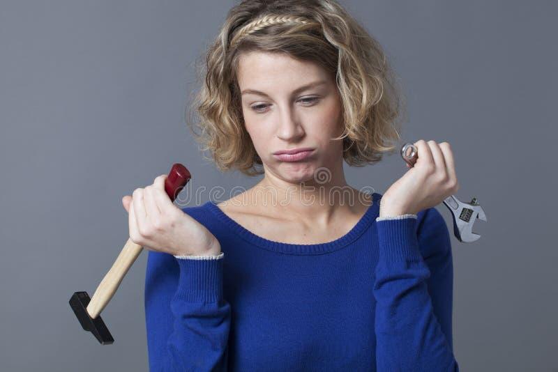 Mujer frustrada 20s que es aburrida en la obra de los mecánicos o DIY fotos de archivo