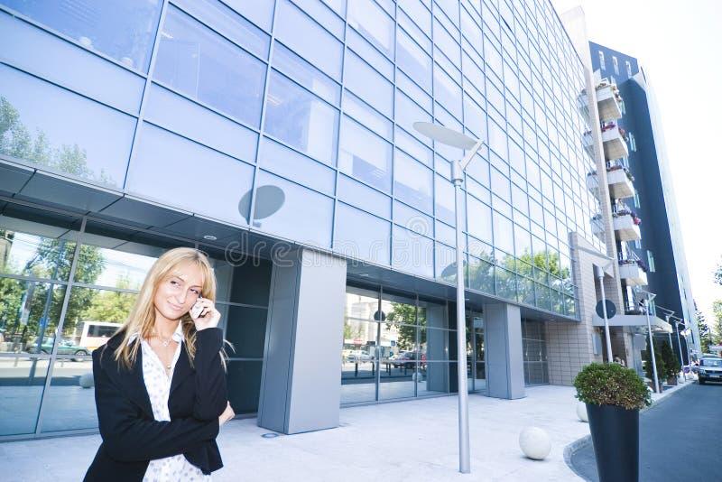 Mujer fuera de la oficina en la célula imagenes de archivo