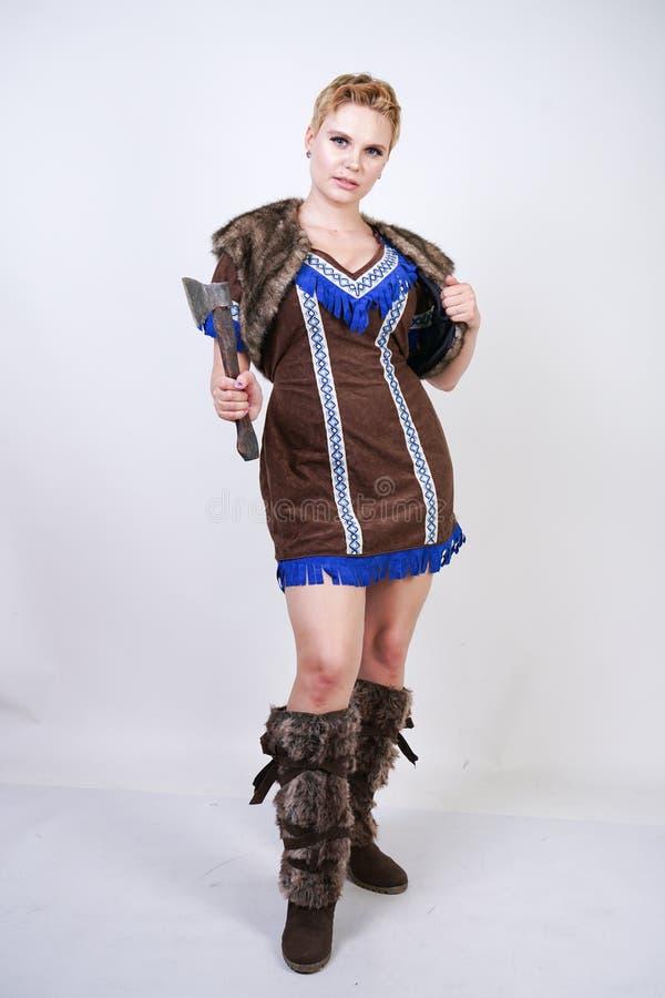Mujer fuerte con el pelo corto y la figura del tamaño extra grande en traje primitivo del cazador con el hacha que presenta agres foto de archivo libre de regalías