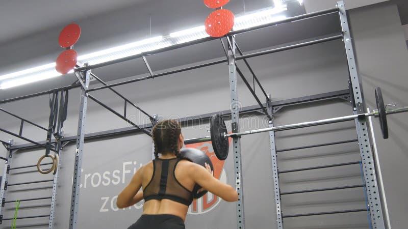 Mujer fuerte joven con el cuerpo perfecto de la aptitud en ropa de deportes que ejercita con la bola de medicina en el gimnasio M imagen de archivo