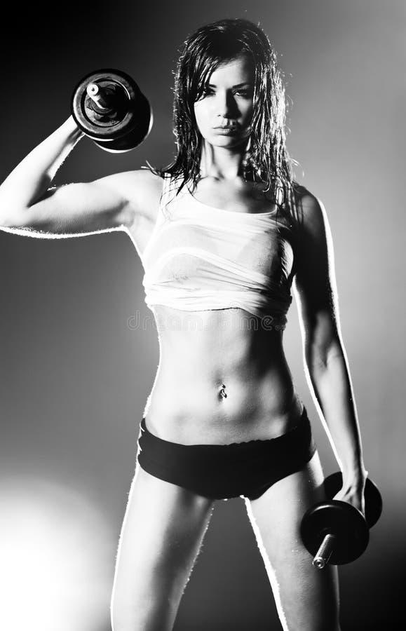 Mujer fuerte joven con pesas de gimnasia imagen de archivo libre de regalías
