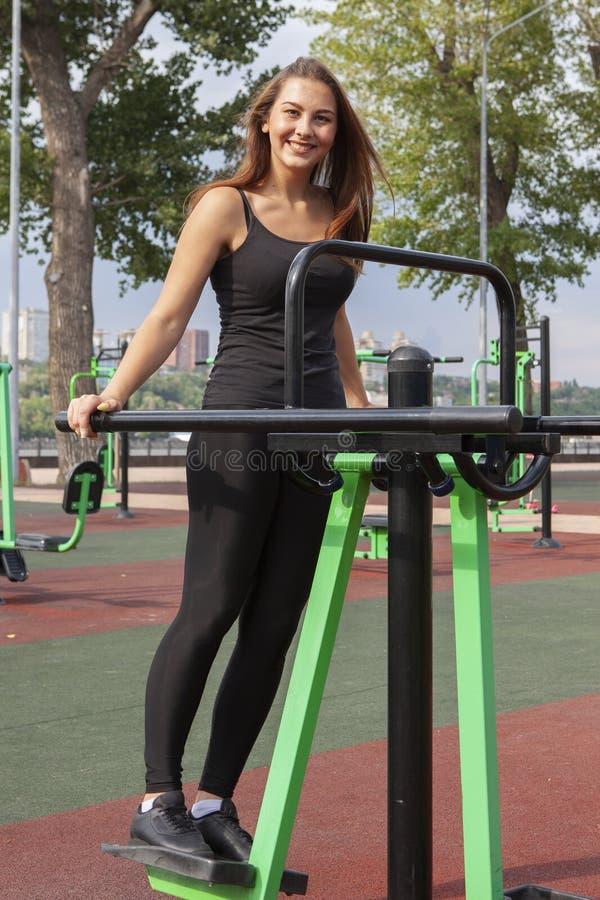 Mujer fuerte que ejercita con el equipo del ejercicio en el parque p?blico Muchacha del atleta en traje del entrenamiento que se  fotografía de archivo libre de regalías