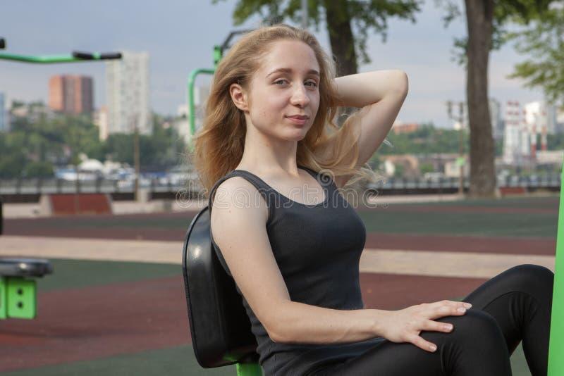 Mujer fuerte que ejercita con el equipo del ejercicio en el parque p?blico Muchacha del atleta en traje del entrenamiento que se  foto de archivo libre de regalías