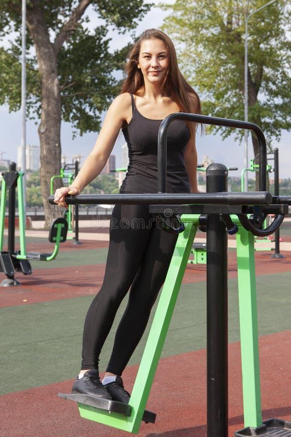 Mujer fuerte que ejercita con el equipo del ejercicio en el parque p?blico Muchacha del atleta en traje del entrenamiento que se  imagen de archivo libre de regalías