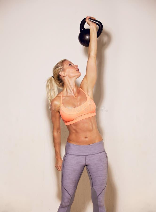 Mujer fuerte que levanta un Kettlebell fotografía de archivo
