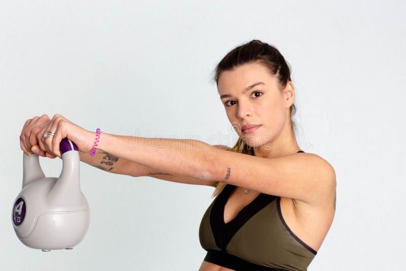 Mujer fuerte que levanta un kettlebell con la mano dos imagen fotos de archivo