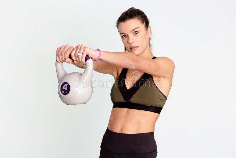 Mujer fuerte que levanta un kettlebell con la mano dos imagen fotografía de archivo libre de regalías
