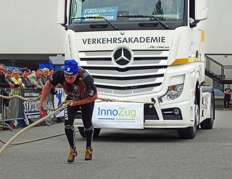 Mujer fuerte que tira de un camión pesado fotografía de archivo libre de regalías