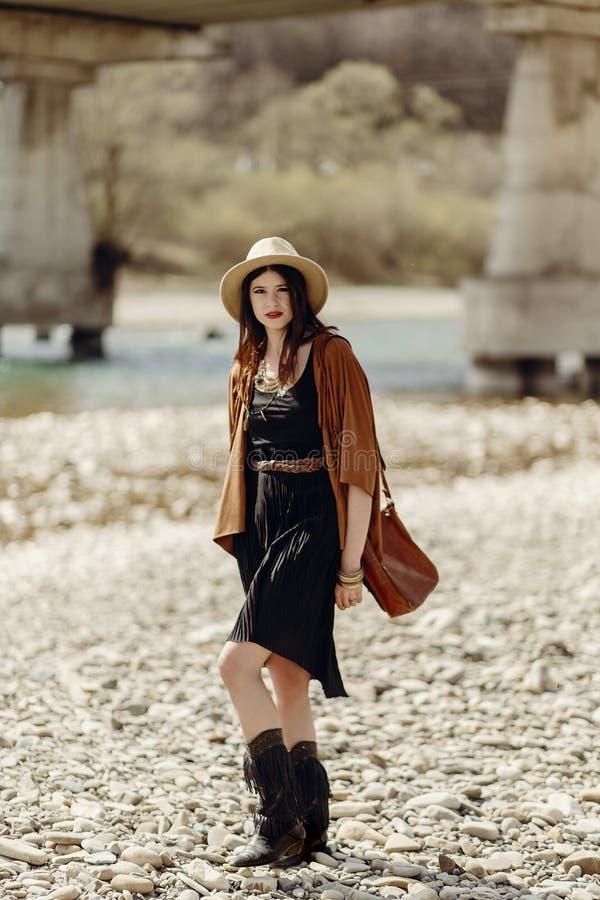 Mujer gitana del boho elegante en sombrero, poncho de la franja y caminar de las botas fotos de archivo libres de regalías