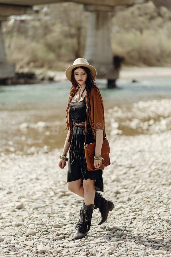 Mujer gitana del boho elegante en sombrero, poncho de la franja y caminar de las botas imagen de archivo