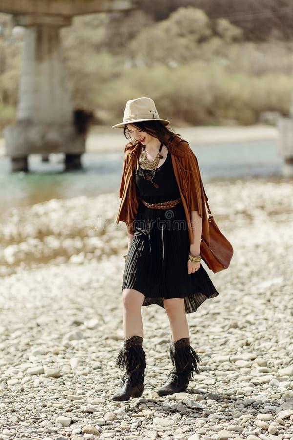 Mujer gitana del boho elegante en sombrero, poncho de la franja y caminar de las botas imágenes de archivo libres de regalías