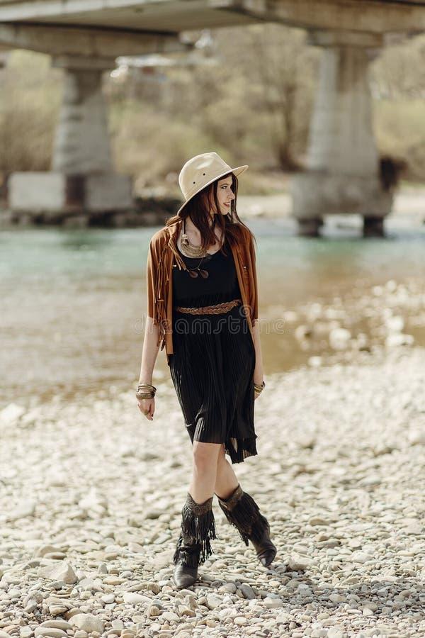 Mujer gitana del boho elegante en sombrero, poncho de la franja y caminar de las botas imagen de archivo libre de regalías