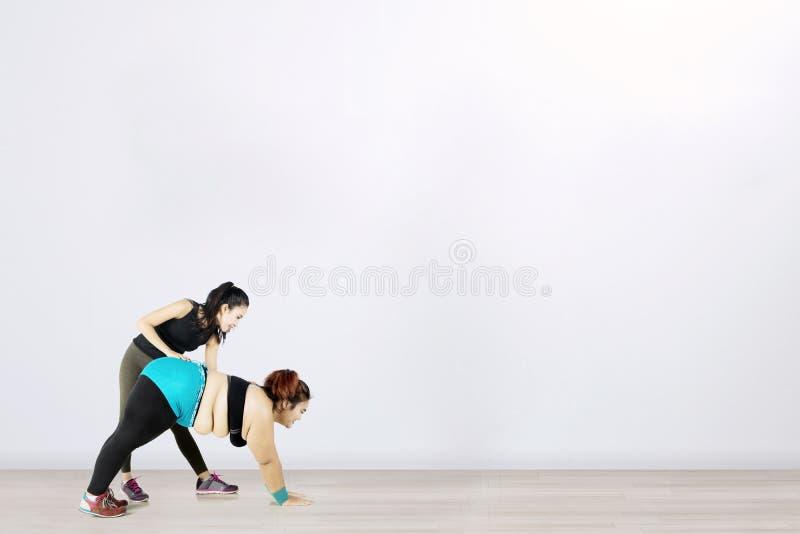 Mujer gorda ayudada por su instructor personal imagen de archivo
