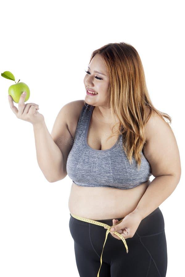 Mujer gorda con la manzana y la cinta de la medida fotos de archivo libres de regalías