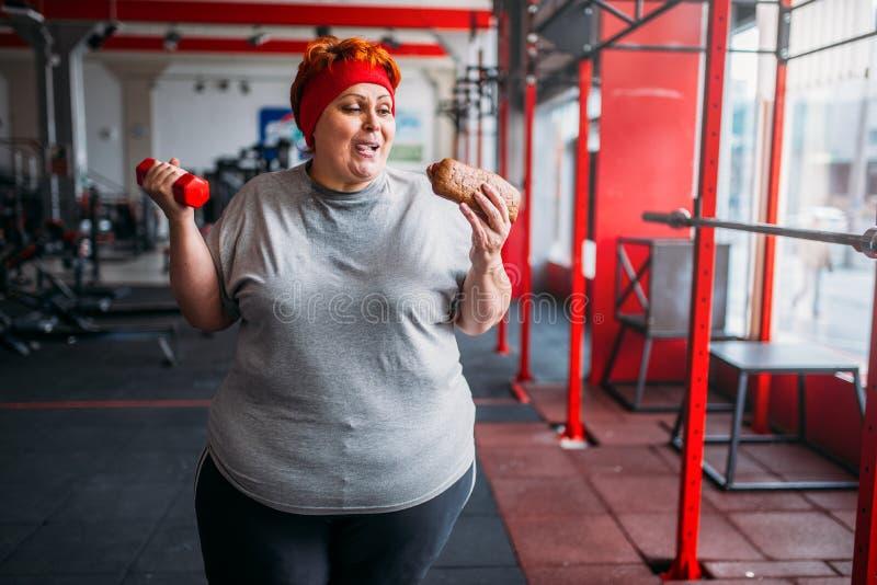 Mujer gorda con los alimentos de preparación rápida y la pesa de gimnasia, motivación imagenes de archivo