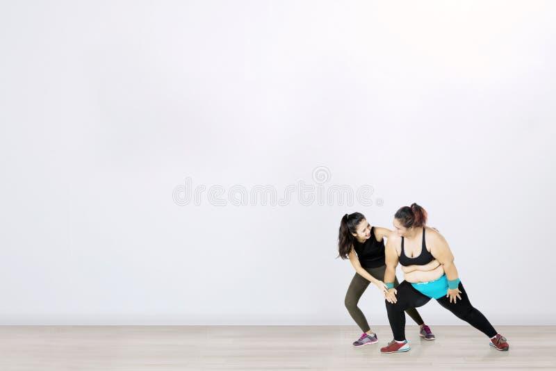 Mujer gorda con su instructor personal foto de archivo libre de regalías