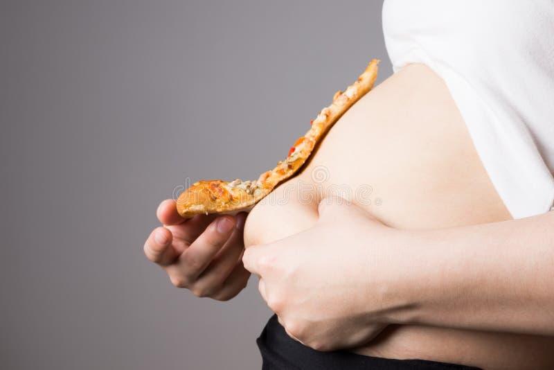 Mujer gorda con un trozo de pizza, concepto de nutrición malsana foto de archivo