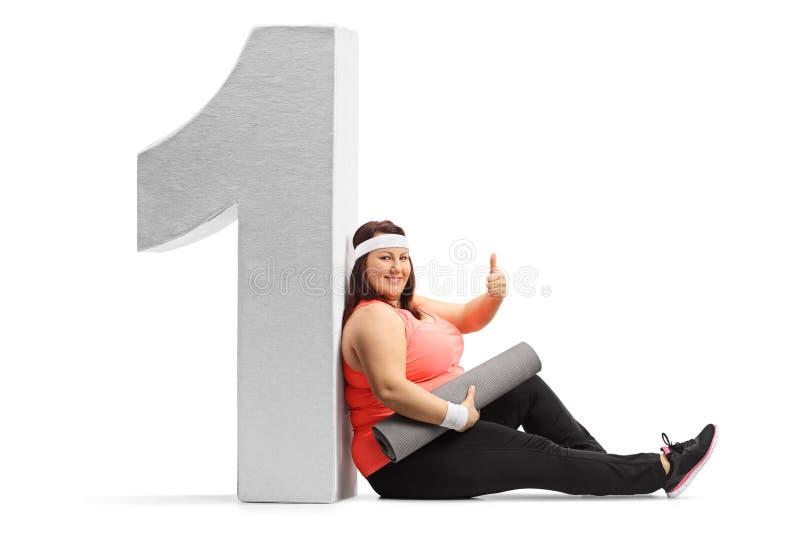 Mujer gorda con una estera del ejercicio que hace un pulgar encima de la muestra y imagen de archivo