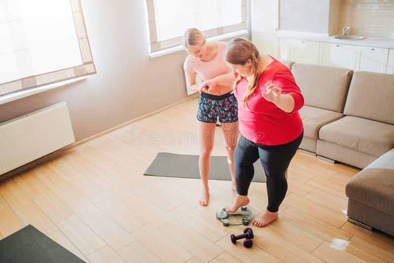 Mujer gorda de la ayuda delgada joven del modelo a colocarse en escala del peso en sala de estar Pesas de gimnasia en piso Modelo foto de archivo libre de regalías