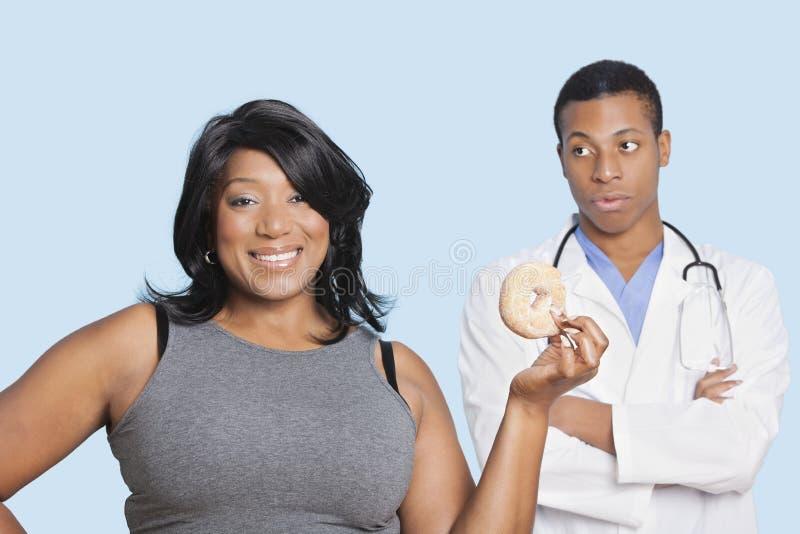 Mujer gorda de la raza mixta con el buñuelo del doctor sobre fondo azul foto de archivo libre de regalías