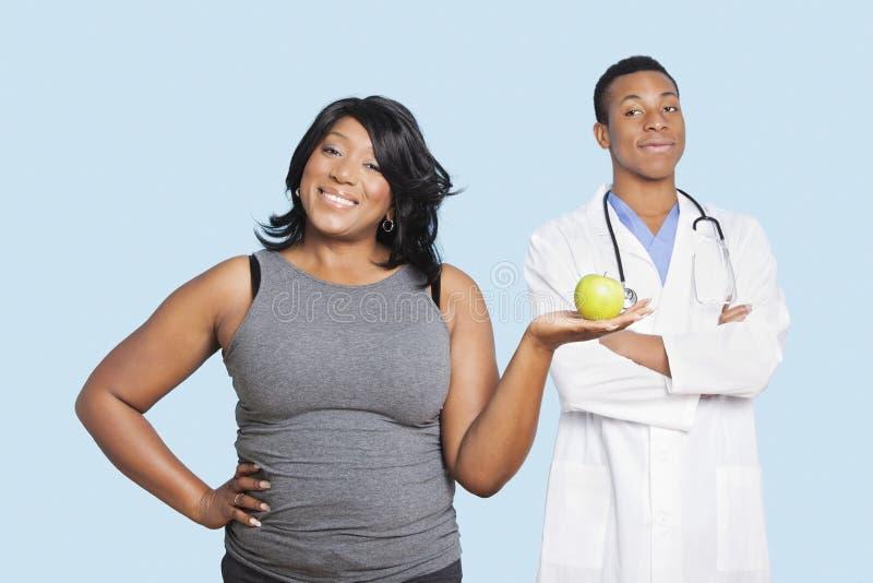 Mujer gorda de la raza mixta que sostiene la manzana verde con el doctor sobre fondo azul fotos de archivo libres de regalías