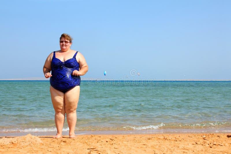 Mujer gorda en la playa imágenes de archivo libres de regalías