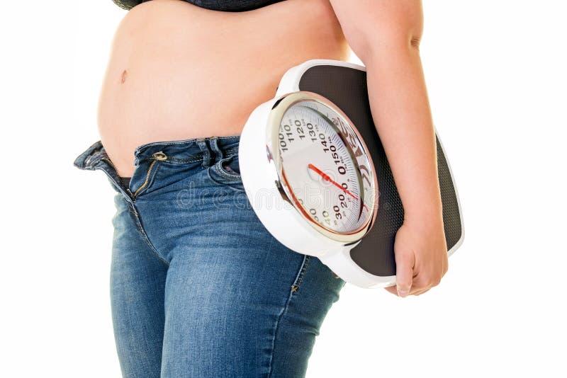 Mujer gorda gorda que lleva una báscula de baño fotografía de archivo