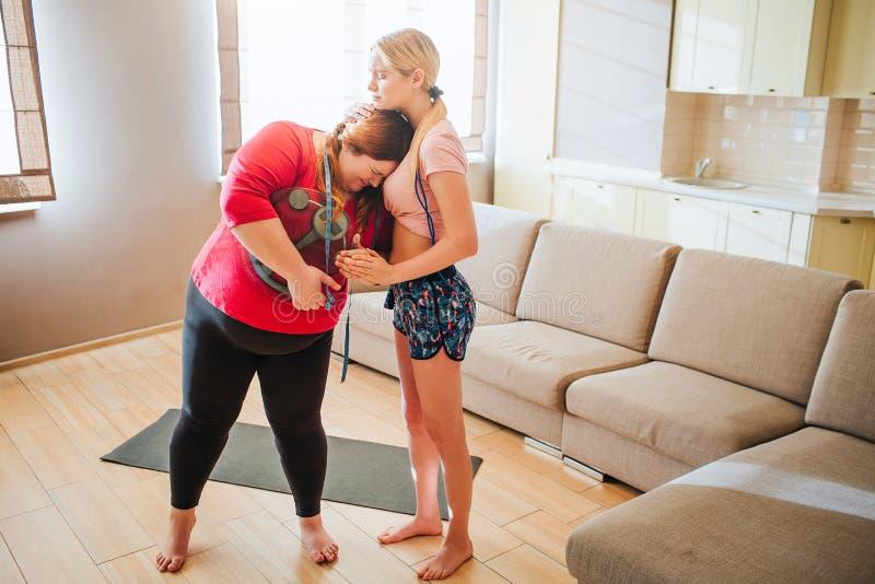 Mujer gorda joven infeliz trastornada que se inclina al modelo y al griterío delgados Ella sostiene la escala del peso en manos y foto de archivo libre de regalías