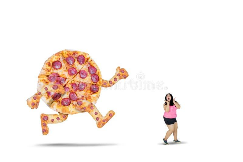 Mujer gorda perseguidora por una pizza grande foto de archivo
