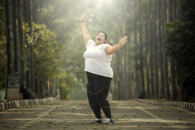 Mujer gorda que celebra su éxito en el camino fotos de archivo libres de regalías