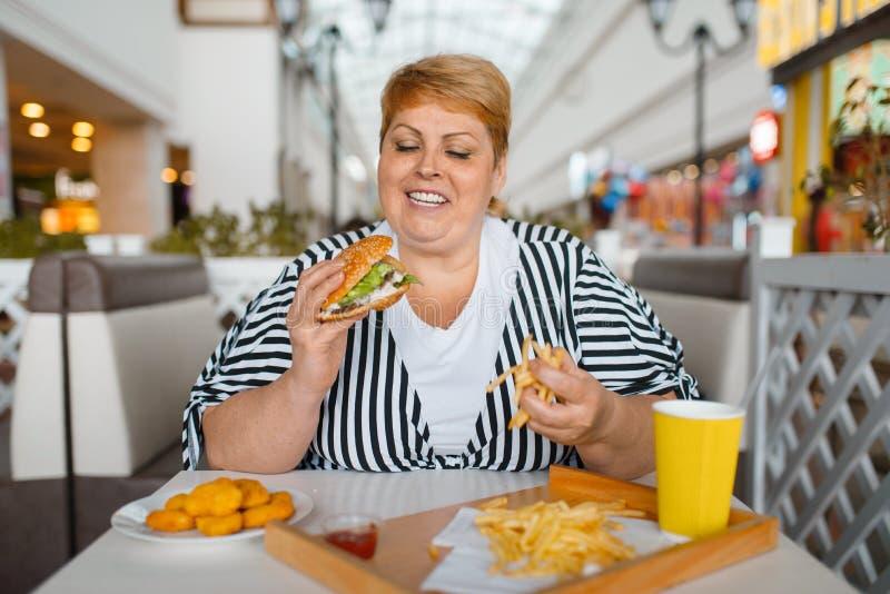 Mujer gorda que come la alta comida de la caloría en restaurante foto de archivo