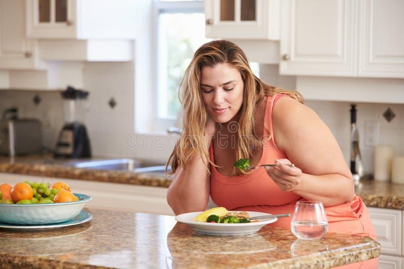Mujer gorda que come la comida sana en cocina fotografía de archivo libre de regalías