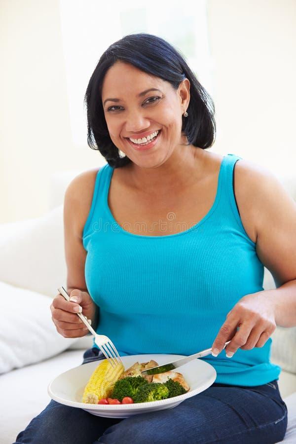 Mujer gorda que come la comida sana que se sienta en el sofá imagen de archivo libre de regalías