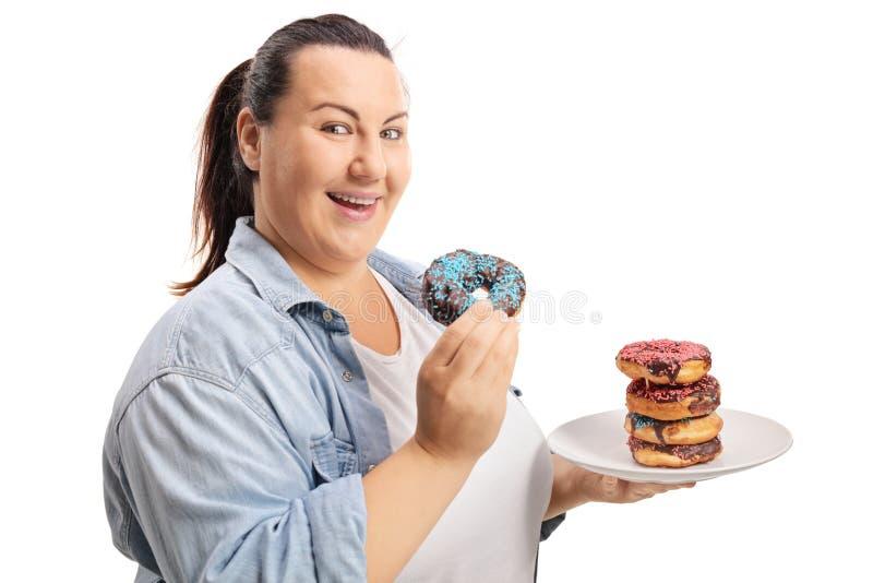 Mujer gorda que come los anillos de espuma fotos de archivo libres de regalías