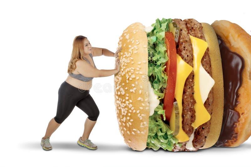 Mujer gorda que empuja las comidas sabrosas en estudio imágenes de archivo libres de regalías