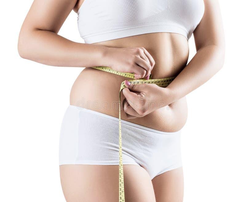 Mujer gorda que mide su vientre gordo imagenes de archivo