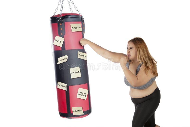 Mujer gorda que perfora sus enfermedades en estudio foto de archivo libre de regalías