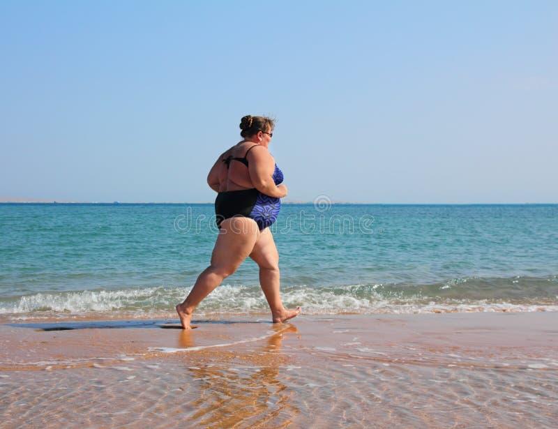 Mujer gorda que se ejecuta en la playa imagenes de archivo