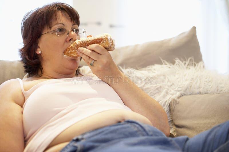 Mujer gorda que se relaja en el sofá imagenes de archivo