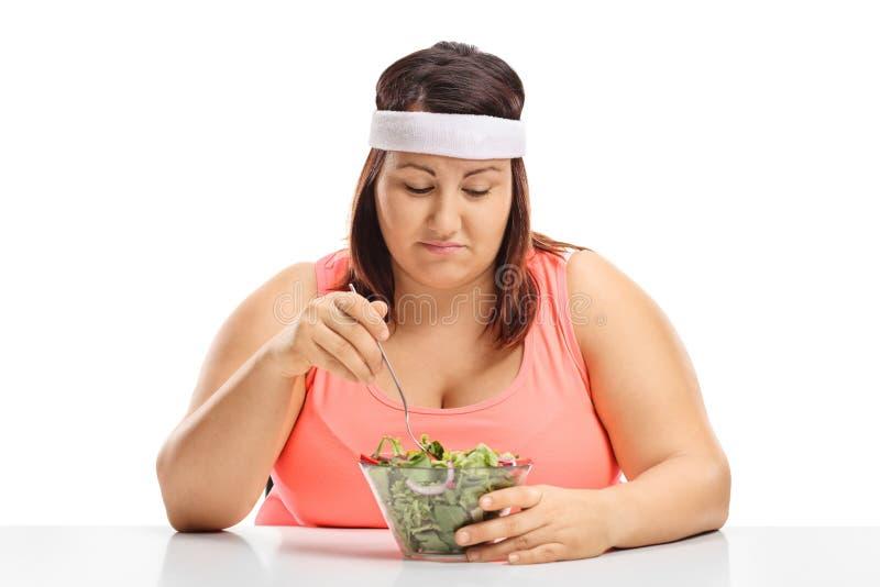 Mujer gorda triste que se sienta en una tabla y que mira un cuenco de imagen de archivo