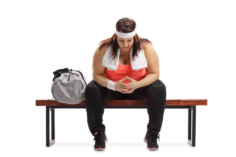 Mujer gorda triste que sienta en un banco de madera al lado de deportes fotografía de archivo