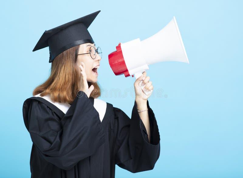 Mujer graduada que grita con el megáfono foto de archivo