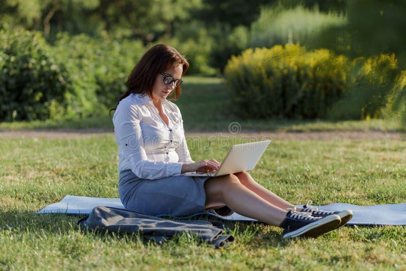 Mujer grande hermosa que miente en la hierba verde en parque con su ordenador portátil y trabajo Muchacha del estudiante que mira imagenes de archivo