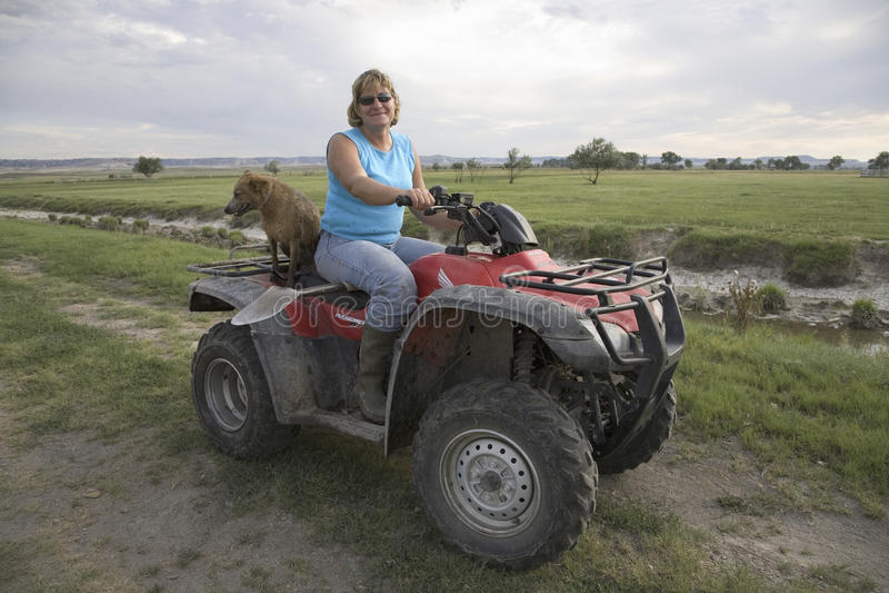 Mujer-granjero en ATV de cuatro ruedas imagenes de archivo