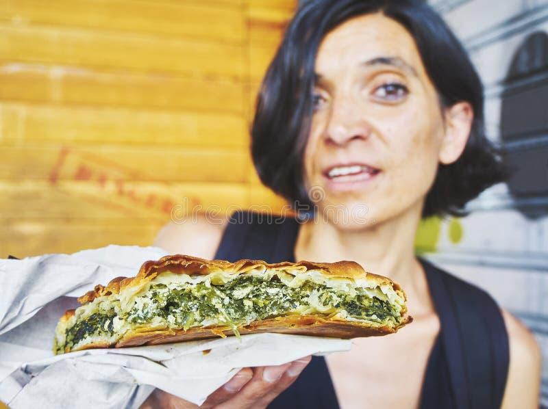 Mujer griega que come una empanada tradicional de Spanakotiropita, de la espinaca y del queso Feta foto de archivo