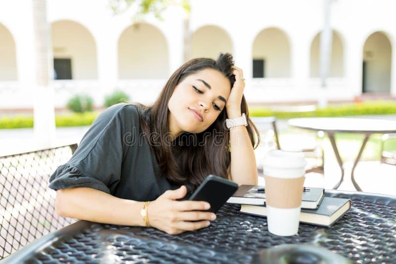 Mujer hermosa aburrida con el contenido en línea en el teléfono móvil fotos de archivo